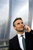 Germany, Bavaria, Businessman using mobile phone, portrait