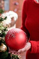 Woman holding large red Christmas bauble