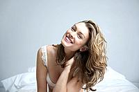 Young woman wearing bra smiling on bed portrait