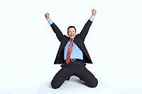 Studio portrait of businessman kneeling and punching air