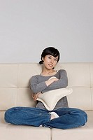 Portrait of young woman sitting on sofa, embracing pillow