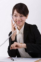 Young businesswoman holding receiver, smiling