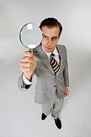 Businessman holding magnifying glass, close_up