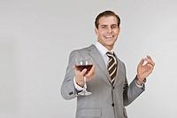 Businessman holding wine glass, portrait
