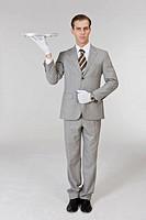 Businessman holding plate, portrait