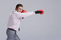 Businessman wearing boxing gloves, portrait