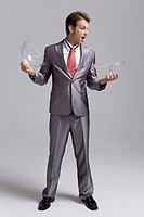 Businessman holding a cakestand and looking surprised