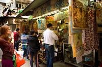Tourists buying memorabilia at the Cat Street market, Soho, Hong Kong, China