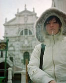 Woman with a hooded jacket on, smoking