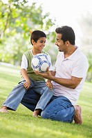 Father and son outdoors in park with ball smiling selective focus
