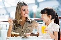 Mother at restaurant with daughter eating dessert and smiling selective focus