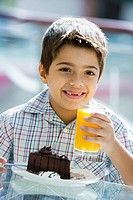 Young boy at restaurant eating dessert and smiling selective focus