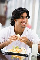 Man at restaurant eating sandwich and smiling selective focus