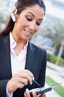 Woman wearing headset outdoors and using personal digital assistant smiling selective focus
