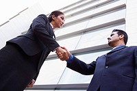 Two businesspeople outdoors by building shaking hands high key/selective focus