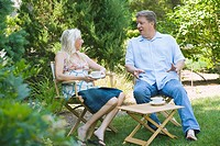 Mature couple sitting in a garden and talking to each other
