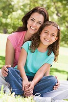 Woman and young girl sitting outdoors smiling