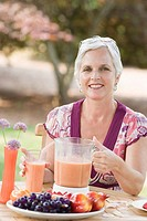 Portrait of a mature woman sitting in a lawn and holding a blender filled with juice