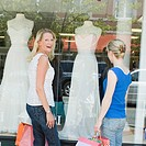 Portrait of a mature woman smiling with a mid adult woman looking at a mannequin in a window display