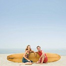 Mature couple sitting on the beach with a surfboard