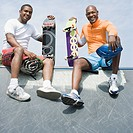Low angle view of two mature men sitting on skateboard ramp and smiling