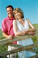 Couple standing outdoors by fence smiling