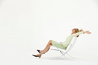 Carefree businesswoman in chair on white background