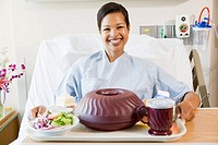 Woman Sitting In Hospital Bed With A Tray Of Food