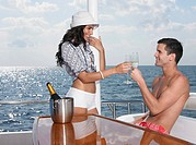 Young couple drinking champagne on yacht