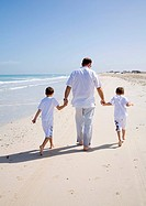 Man walking with children on beach, rear view