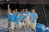 Sailing team celebrating with trophy on boat