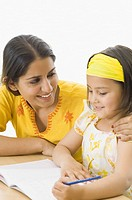 Young woman teaching her daughter and smiling