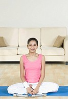 Young woman sitting on an exercise mat