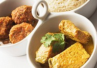 Close_up of boiled rice and meatballs with fish curry served in bowls