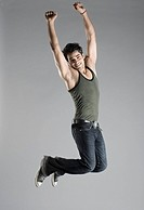 Portrait of a young man jumping with his arms raised and smiling