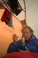 An unhappy man eating noodles in a tent