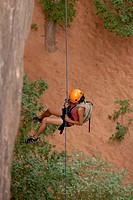 Tourist hanging on a rope while Canyoning in the area of the slick rock trail near Arches Bows National Park MoabUtahUSA MR