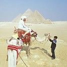 Mother and daughter 5 yrs riding camel below pyramids of Giza young Egyptian boy attending to their camel The Great pyramid middle in view is the only...