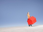 Woman holding small model house in desert