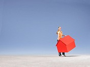 Woman carrying small model house in desert