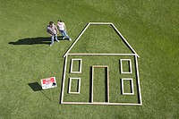 Couple standing next to house outline