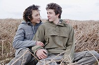 Teenage couple sitting in field