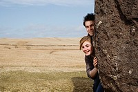 Teenage couple peering from behind rock