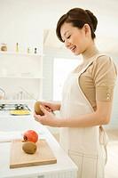 A woman peeling a kiwi fruit in the kitchen, side view