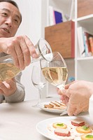 Closed Up Image of a Mature Adult Man Pouring White Wine, Differential Focus, Low Angle View