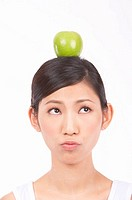 Portrait of Natural Young girl with an Apple on Her Head