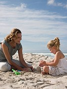 Mother and daughter playing in sand