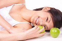 Portrait of Natural Young girl lying on Floor, Holding Apple