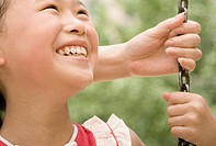 Close_up of a girl smiling on a swing