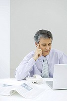 Businessman sitting at desk, looking at laptop computer, holding head